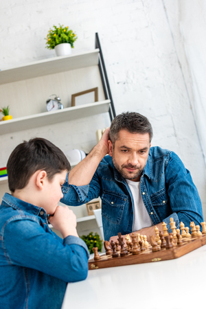 handsome father and son playing chess while sitting at table at home 版權商用圖片