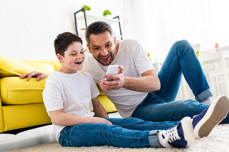 Heureux père et fils utilisant un smartphone dans le salon