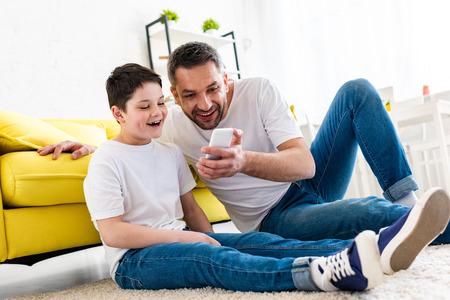 Szczęśliwy ojciec i syn korzystający ze smartfona w salonie