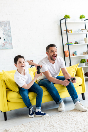 excited father and son playing Video Game on couch in Living Room 版權商用圖片