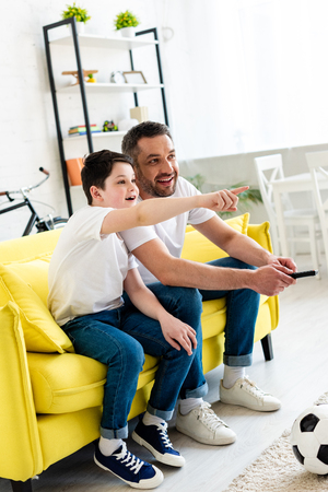 Son pointing with finger while sitting on couch and watching tv with father at home