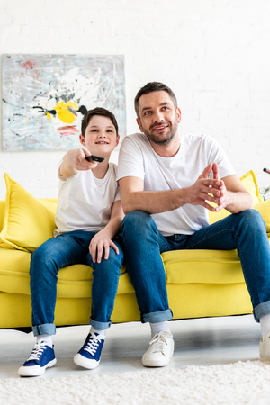 Father and son sitting on couch and watching tv at home
