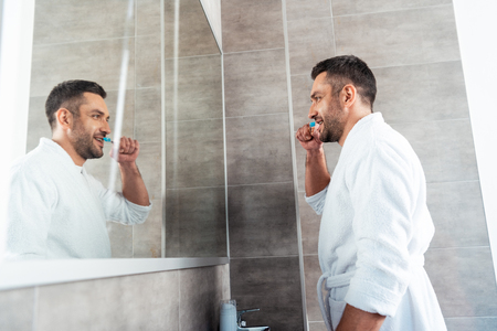 Handsome man in white bathrobe brushing teeth in bathroom during morning routine