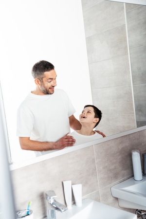 Handsome father embracing son in bathroom during morning routine Фото со стока