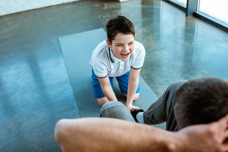 Son shouting while helping father doing sit up exercise at gym