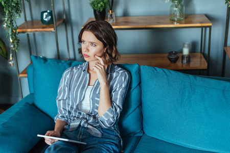 overhead view of pensive brunette woman holding digital tablet while sitting in living room