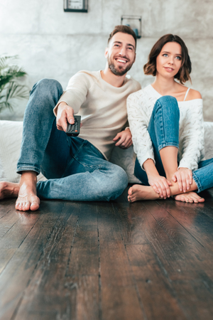Low angle view of cheerful man sitting on floor near attractive woman and holding remote controller 版權商用圖片