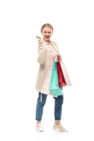 Happy middle aged woman with shopping bags and Credit card isolated on white background Banco de Imagens