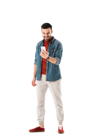 Irritated man in denim shirt using smartphone isolated on white background
