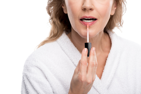 Cropped view of mature woman applying lip gloss isolated on white background Stok Fotoğraf
