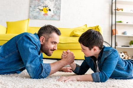 Father and son lying on carpet and arm wrestling at home Фото со стока