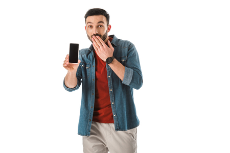 Surprised bearded man covering mouth with hand while holding smartphone with blank screen isolated on white background Stock Photo
