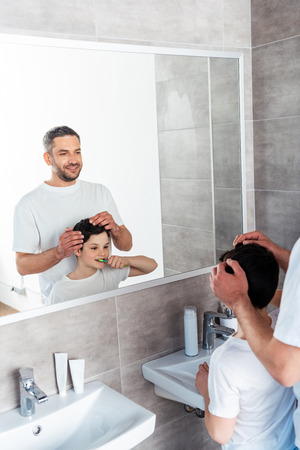 Smiling father adjusting hairstyle of son in bathroom in morning