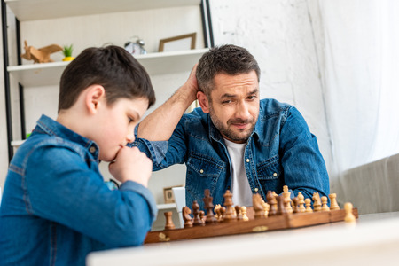 Selective focus of father and son in denim playing chess at home