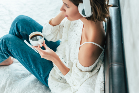 Overhead view of brunette woman in headphones holding cup and listening music