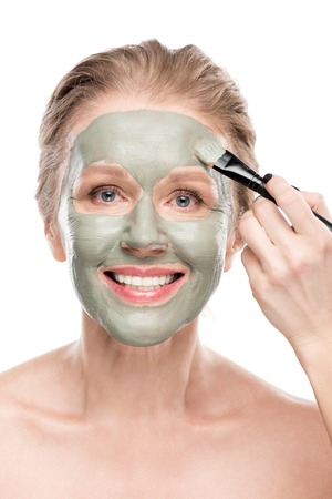 Smiling mature woman Applying clay mask with cosmetic brush isolated on white background
