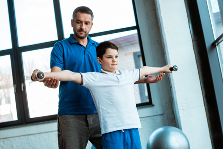 Father helping son exercising with dumbbells at gym