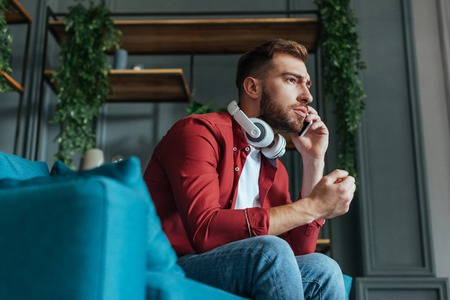 low angle view of bearded man in headphones sitting on sofa and talking on smartphone in living room