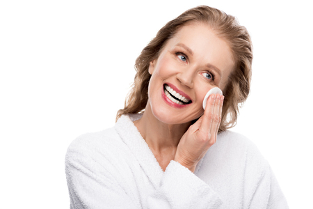 Beautiful mature woman wiping face with cotton pad isolated on white background