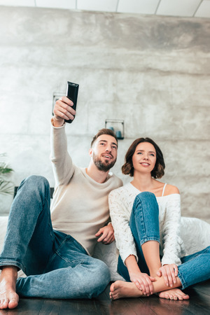 Low angle view of happy man sitting on floor near cheerful woman and holding remote controller 版權商用圖片
