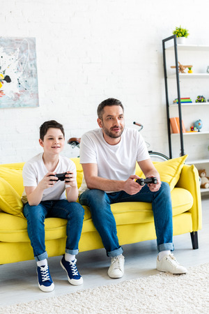 Father and son with joysticks playing Video Game on couch in Living Room