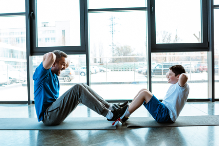Father and son doing sit up exercise on fitness mats at gym