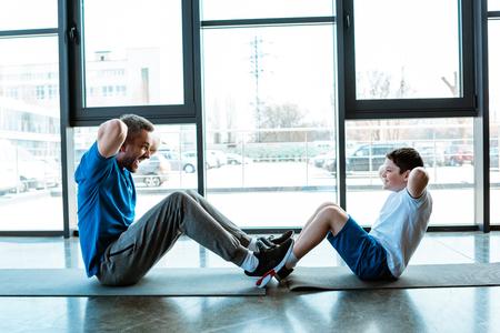 Vader en zoon doen sit-up oefening op fitnessmatten in de sportschool