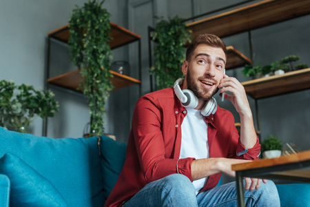 low angle view of happy bearded man in headphones talking on smartphone in living room