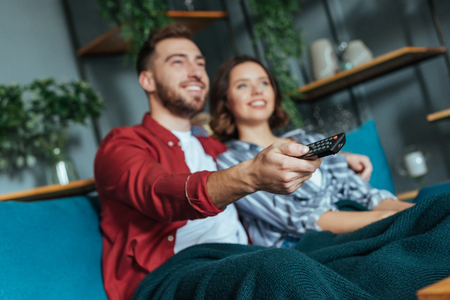 Selective focus of happy man holding remote controller while watching movie with woman