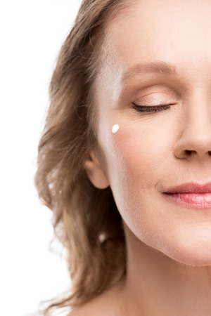 Cropped view of mature woman with cosmetic cream on face isolated on white background