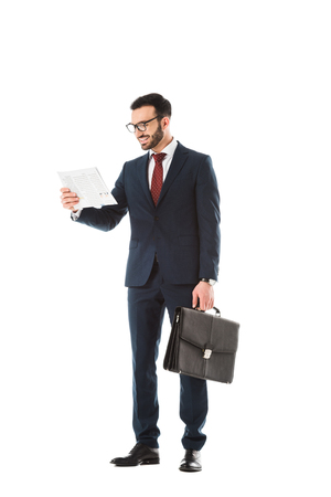 Cheerful businessman with briefcase reading newspaper isolated on white background