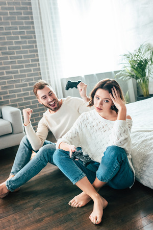 Happy man looking at upset girl sitting on floor with joystick