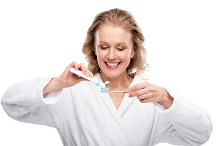Middle aged woman with toothbrush and toothpaste isolated on white background