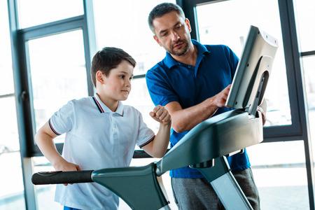 Ojciec wskazujący na ekran bieżni, podczas gdy syn biega w centrum sportowym Zdjęcie Seryjne