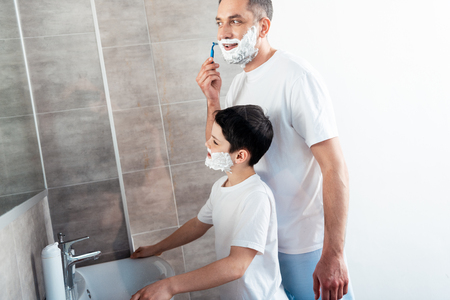 Son with shaving cream on face near father shaving with razor in bathroom