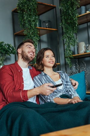 Low angle view of cheerful man holding remote controller while watching movie with woman at home
