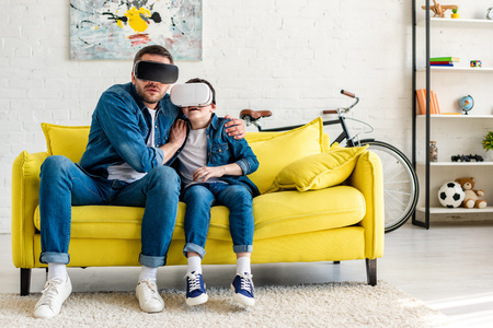 frightened father and son in vr headsets experiencing Virtual reality on couch at home