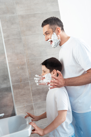 Smiling father applying shaving cream on face of son in bathroom in morning