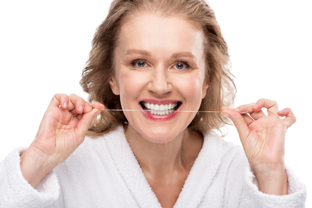Middle aged woman using dental floss isolated on white background