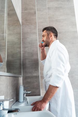 Handsome man in white bathrobe brushing teeth in bathroom during morning routine