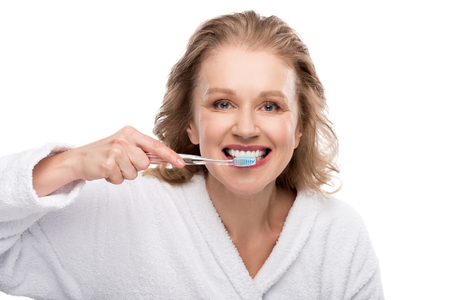 Frau mittleren Alters Zähneputzen isoliert auf weißem Hintergrund