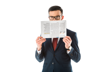 Businessman in black suit and glasses hiding face behind newspaper and looking at camera isolated on white background