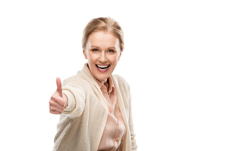 Excited middle aged woman showing thumb up sign isolated on white background Imagens