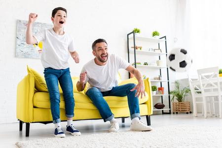 Padre e hijo emocionados vitoreando mientras ve partidos deportivos en la sala de estar