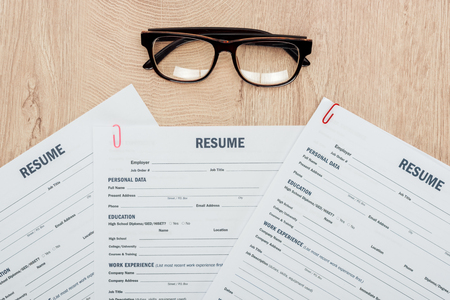 Top view of print resume templates and glasses on wooden table