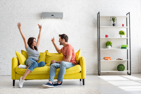Happy man and woman talking while sitting on yellow sofa under air conditioner at home Stockfoto
