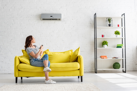 Pretty young woman sitting on yellow sofa under air conditioner at home Stock fotó
