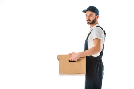 Serious delivery man in overall holding carton box and looking at camera isolated on white background