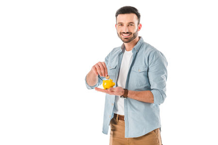 Cheerful bearded man putting coin into piggy bank and looking at camera isolated on white background Stok Fotoğraf