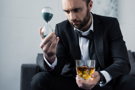 Selective focus of upset businessman looking at hourglass while holding glass of whiskey Stockfoto